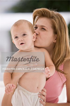 Woman kissing her daughter Stock Photo - Premium Royalty-Free, Image code: 6108-05874024