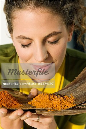 Close-up of a woman smelling spices Stock Photo - Premium Royalty-Free, Image code: 6108-05874197
