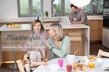 Family at a breakfast table Stock Photo - Premium Royalty-Free, Image code: 6108-05874619