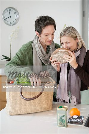 Woman smelling a loaf of bread with her husband standing beside her Stock Photo - Premium Royalty-Free, Image code: 6108-05874623