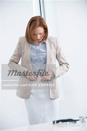 Woman getting dressed in an office Stock Photo - Premium Royalty-Free, Image code: 6108-05874766