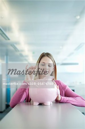 Businesswoman inserting a coin into a piggy bank Stock Photo - Premium Royalty-Free, Image code: 6108-05874788