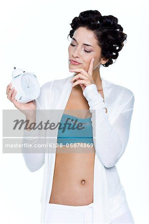 Young woman with hair clips, holding alarm clock Stock Photo - Premium Royalty-Free, Image code: 6108-05874869