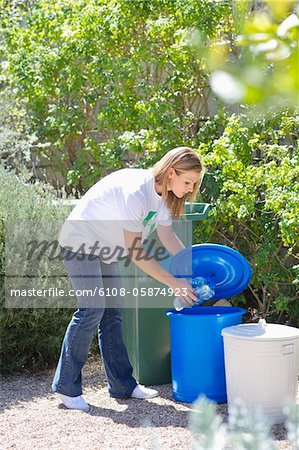 Woman throwing water bottles in garbage bin Stock Photo - Premium Royalty-Free, Image code: 6108-05874923