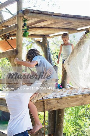 Rear view of a boy grasping rope to reach tree house Stock Photo - Premium Royalty-Free, Image code: 6108-05874928