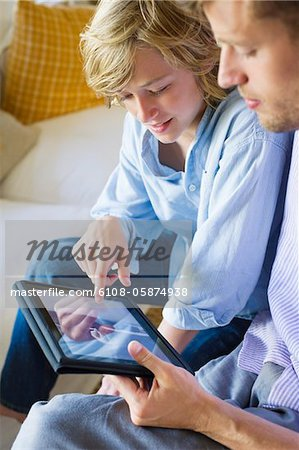 Man and a little boy looking at digital tablet Stock Photo - Premium Royalty-Free, Image code: 6108-05874938