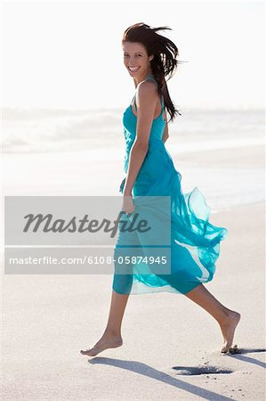 Portrait of a young woman walking on beach Stock Photo - Premium Royalty-Free, Image code: 6108-05874945