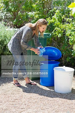 Woman throwing water bottles in garbage bin Stock Photo - Premium Royalty-Free, Image code: 6108-05875009