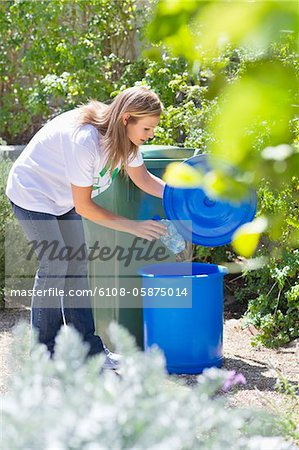 Woman throwing water bottle in garbage bin Stock Photo - Premium Royalty-Free, Image code: 6108-05875014