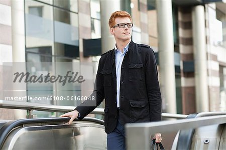 Businessman standing on escalator Stock Photo - Premium Royalty-Free, Image code: 6108-06166048
