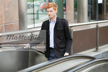 Businessman standing on escalator moving up Stock Photo - Premium Royalty-Free, Image code: 6108-06166059