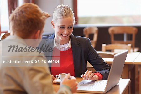 Couple sitting in a restaurant working on a laptop Stock Photo - Premium Royalty-Free, Image code: 6108-06166064