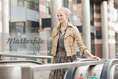 Businesswoman standing on escalator Stock Photo - Premium Royalty-Free, Image code: 6108-06166099