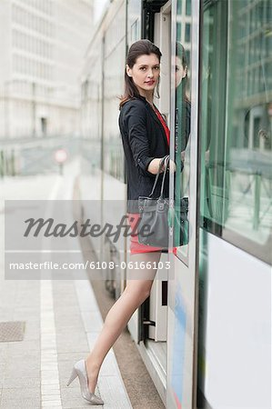 Woman boarding a tram Stock Photo - Premium Royalty-Free, Image code: 6108-06166103