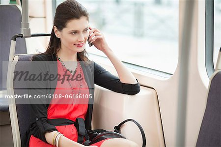 Woman traveling in a tram and talking on a mobile phone Stock Photo - Premium Royalty-Free, Image code: 6108-06166105