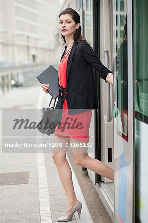 Woman exiting from a bus Stock Photo - Premium Royalty-Free, Image code: 6108-06166132