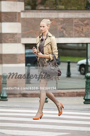 Businesswoman crossing the road Stock Photo - Premium Royalty-Free, Image code: 6108-06166134
