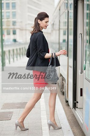 Woman boarding a bus Stock Photo - Premium Royalty-Free, Image code: 6108-06166149