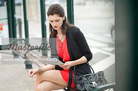 Woman sitting at bus stop and reading a newspaper Stock Photo - Premium Royalty-Free, Image code: 6108-06166153