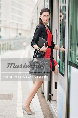 Woman boarding a bus Stock Photo - Premium Royalty-Free, Image code: 6108-06166157