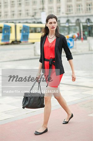 Woman walking on a street Stock Photo - Premium Royalty-Free, Image code: 6108-06166160