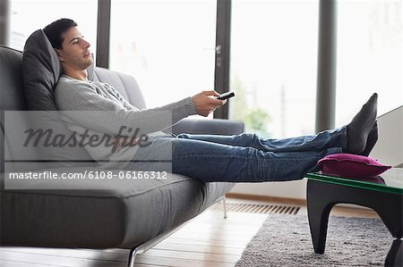 Man reclining on a couch and watching television Stock Photo - Premium Royalty-Free, Image code: 6108-06166312