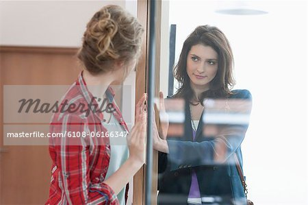 Two female friends looking at each other through a glass door Stock Photo - Premium Royalty-Free, Image code: 6108-06166347