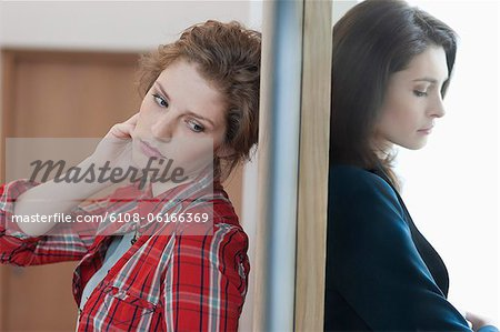 Two female friends standing back to back against a door Stock Photo - Premium Royalty-Free, Image code: 6108-06166369