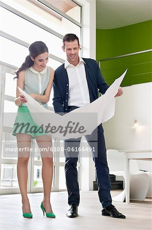 Couple reading a blueprint Stock Photo - Premium Royalty-Free, Image code: 6108-06166491