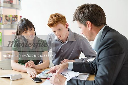 Real estate agent discussing property documents to his clients Stock Photo - Premium Royalty-Free, Image code: 6108-06166567