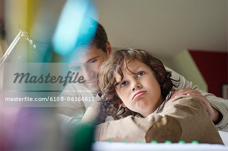 Boy thinking while studying with his father at home Stock Photo - Premium Royalty-Free, Image code: 6108-06166611