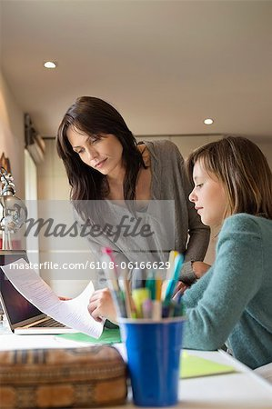 Girl studying with her mother at home Stock Photo - Premium Royalty-Free, Image code: 6108-06166629