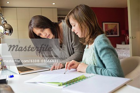 Girl studying with her mother at home Stock Photo - Premium Royalty-Free, Image code: 6108-06166631