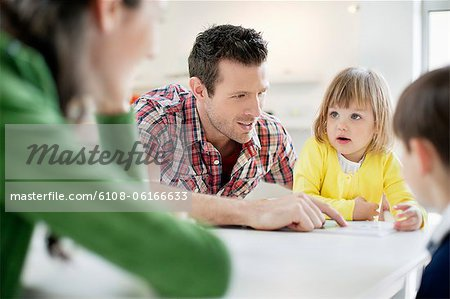 Couple teaching their children at home Stock Photo - Premium Royalty-Free, Image code: 6108-06166633