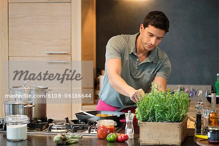 Man preparing food in the kitchen Stock Photo - Premium Royalty-Free, Image code: 6108-06166644