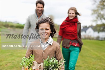 Portrait of a boy holding a basket of vegetables with his parents in a farm Stock Photo - Premium Royalty-Free, Image code: 6108-06166668