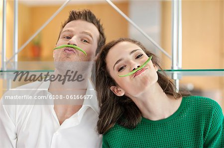 Couple playing with green bean in the kitchen Stock Photo - Premium Royalty-Free, Image code: 6108-06166677