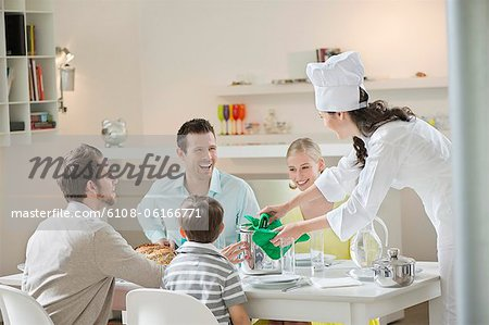 Woman serving lunch at dining table Stock Photo - Premium Royalty-Free, Image code: 6108-06166771