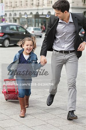 Girl pulling a trolley bag while running with her father Stock Photo - Premium Royalty-Free, Image code: 6108-06166796
