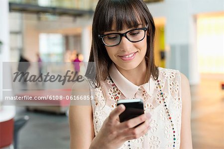 Businesswoman text messaging in an office Stock Photo - Premium Royalty-Free, Image code: 6108-06166859