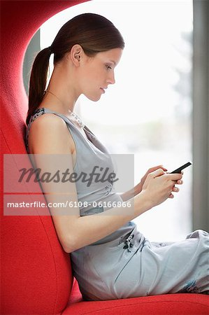 Businesswoman text messaging on a mobile phone in an office Stock Photo - Premium Royalty-Free, Image code: 6108-06166866