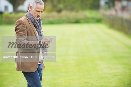 Man text messaging on a mobile phone in a park Stock Photo - Premium Royalty-Free, Image code: 6108-06166896