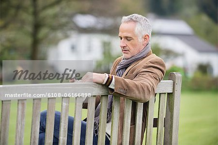 Man text messaging on a mobile phone in a park Stock Photo - Premium Royalty-Free, Image code: 6108-06166898
