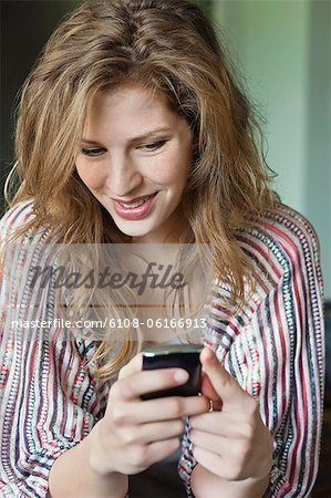 Close-up of a beautiful woman text messaging on a mobile phone Stock Photo - Premium Royalty-Free, Image code: 6108-06166913