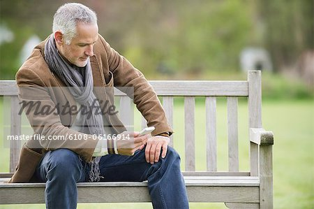 Man text messaging on a mobile phone in a park Stock Photo - Premium Royalty-Free, Image code: 6108-06166914