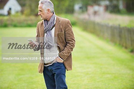 Man text messaging on a mobile phone in a lawn Stock Photo - Premium Royalty-Free, Image code: 6108-06166919