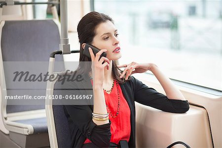 Woman traveling in a bus and talking on a mobile phone Stock Photo - Premium Royalty-Free, Image code: 6108-06166967
