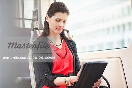 Woman traveling in a bus using a digital tablet Stock Photo - Premium Royalty-Free, Image code: 6108-06166986