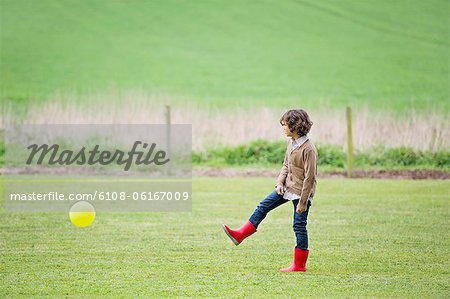 Boy playing with a ball in a field Stock Photo - Premium Royalty-Free, Image code: 6108-06167009