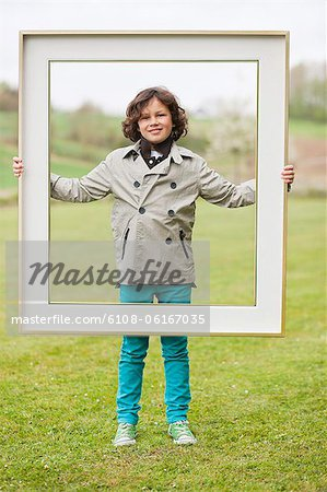 Portrait of a boy standing with a frame in a park Stock Photo - Premium Royalty-Free, Image code: 6108-06167035
